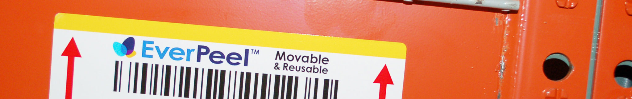 White Barcoded removable and reusable label with barcode and product name affixed to warehouse shelving